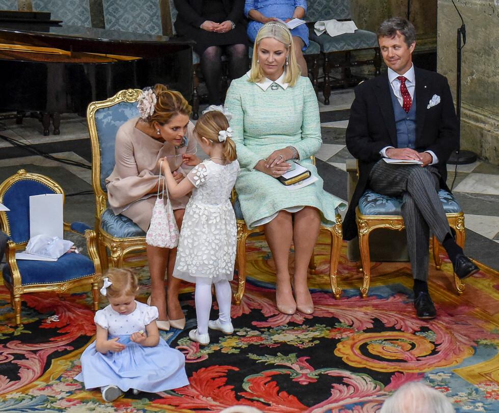 UHØYTIDELIG: Det er så utrolig deilig å se at kongefamiliene lar barna få lov til å være barn - også i høytidelige settinger. Her snakker prinsesse Estelle med tante Madeleine, mens prinsesse Leonore har satt seg på gulvet. Anledningen er prins Oscars dåp i Stockholm i mai. I bakgrunnen gudmor kronprinsesse Mette-Marit og gudfar kronprins Frederik av Danmark. Foto: NTB Scanpix