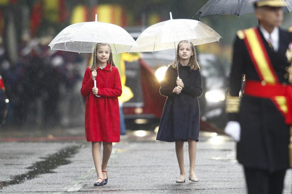 SØSTRENE SISTERS: Kronprinsesse Leonor (11) og prinsesse Sofia (9) trosset regn og surt vær for å ta del i militærparaden under Spanias nasjonaldag 12. oktober. Søte! Foto: NTB Scanpix