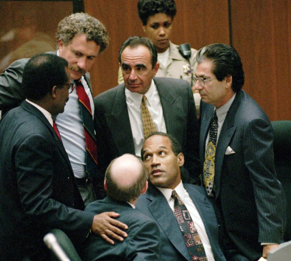 BESKYTTENDE RING: O.J. Simpson omringet av mennene som skulle hjelpe ham med å bli frikjent. Mannen til høyre med brillene er Robert Kardashian, mens mannen med det gule slipset er Robert Shapiro - begge Simpsons advokater. Også på bildet: Johnnie L. Cochran Jr., Peter Neufeld og Robert Blasier,  Foto: NTB Scanpix