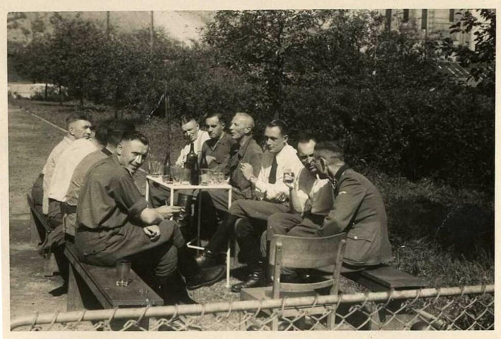MATPAUSE: Det mest bemerkelsesverdige med disse bildene er at de alle er tatt i Auschwitz, men at fotografen har klart å ta bildene uten å dokumentere elendigheten som foregår i konsentrasjonsleiren i samme øyeblikk. SS-offiser Karl-Friedrich Höcker (nærmest kamera til venstre), Dr. Fritz Klein (nederst til venstre) og Dr. Eduard Wirths (med slips) under en matpause i Auschwitz.  Foto: NTB Scanpix
