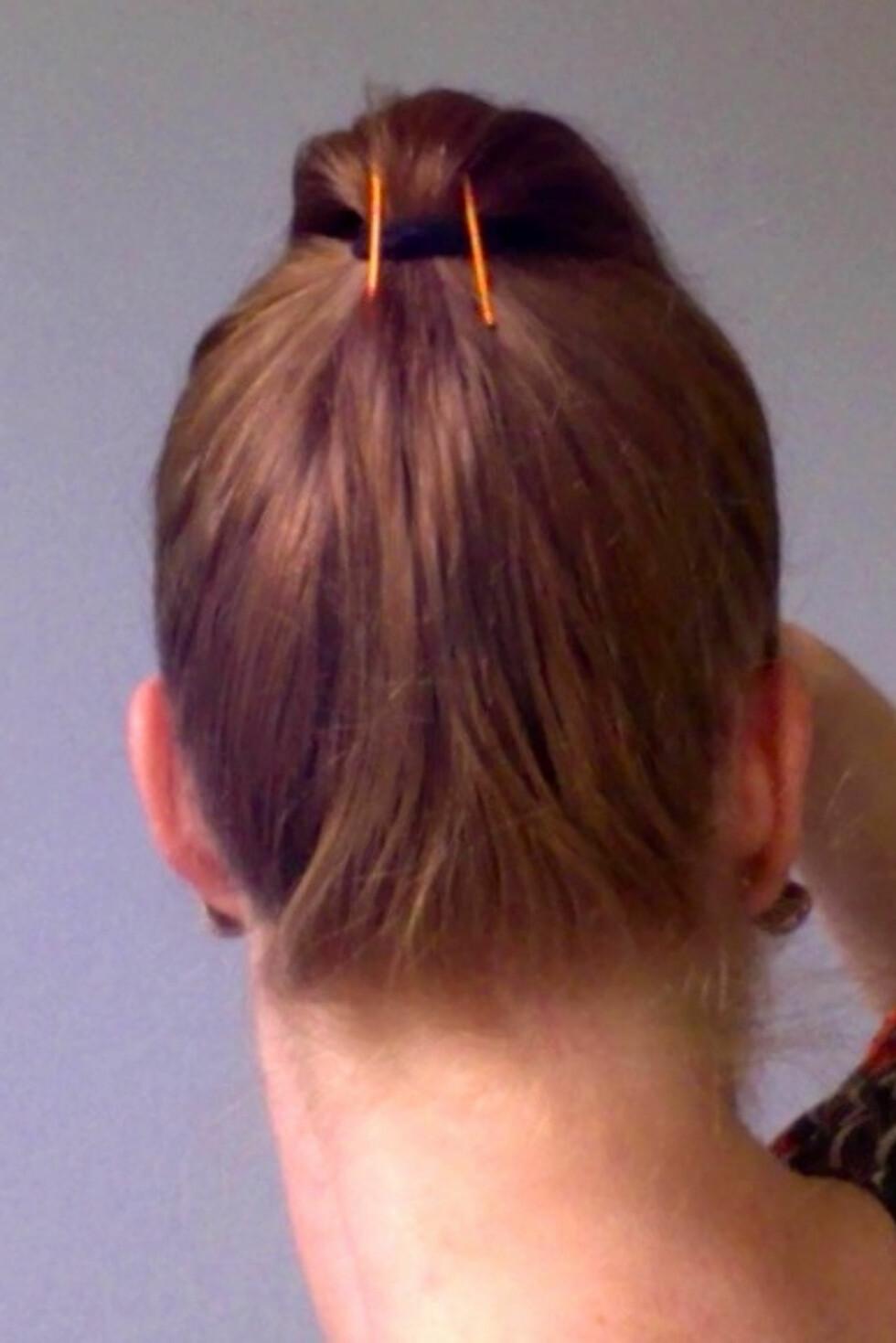Flipp håret framover mens du fester to hårnåler på undersiden av hestehalen, gjennom hårstrikken. La dem stikke litt opp for å gi deg løftet.  Foto: Aina Kristiansen