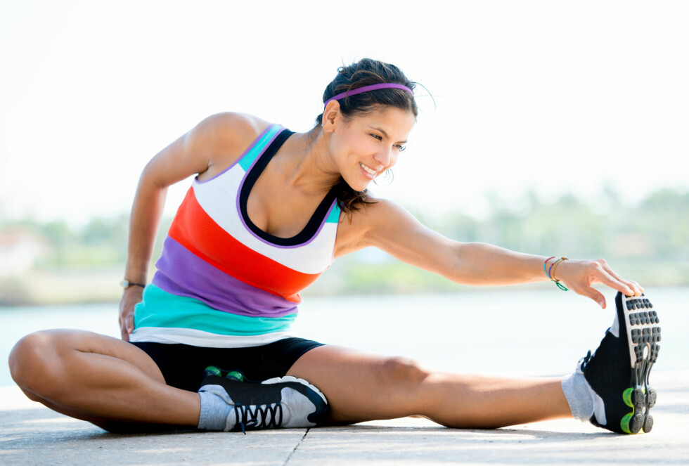Fit woman doing stretching exercises outdoors and smiling Foto: Fotolia