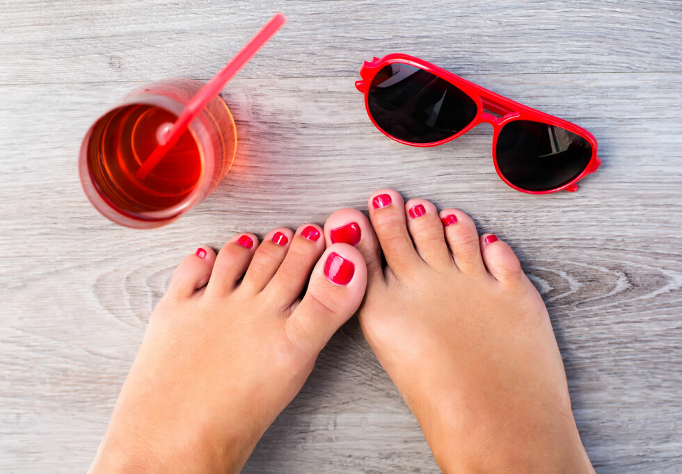 Female feet with color pedicure near with glasses and fresh drink Foto: mariiya - Fotolia