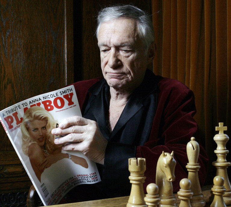 MED SLÅBROKEN PÅ: Hefner i sitt signaturplagg, mens han blar i spesialutgaven viet Anna Nicole Smith i 2007.
