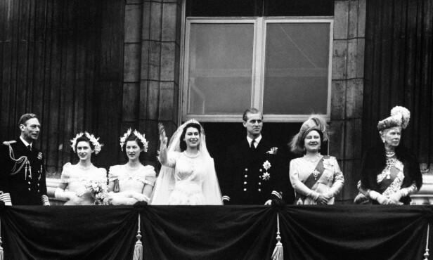MOTTOK HYLLEST FRA FOLKET: Det nygifte paret vinker til folket fra balkongen på Buckingham Palace kort tid etter bryllupsseremonien. Fra venstre: kong George VI, brudens søster prinsesse Margaret, en av de andre brudepikene, brudeparet, dronning Elizabeth (senere kjent som dronningmoren) og enkedronning Mary (kongens mor). Foto: NTB Scanpix