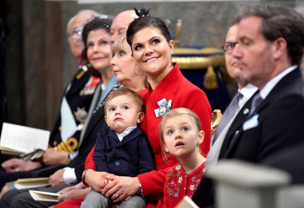 VAKKER: Kronprinsesse Victoria strålte i et julerødt antrekk under nevøens barnedåp. Datteren prinsesse Estelle var ikledd en grå kjole med en søt, rød cardigan til. Prins Oscar satt rolig på fanget til mamma Victoria, og lot seg tydelig fascinere av musikken som fylte slottskyrkan. Foto: NTB Scanpix