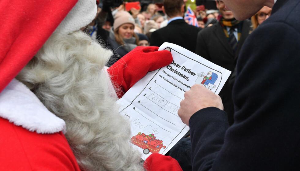 ETT ØNSKE: Prins William viser julenissen i Finland at sønnen ønsker seg en politibil til jul. Legg for øvrig merke til prins Georges skjønne underskrift! Foto: NTB Scanpix