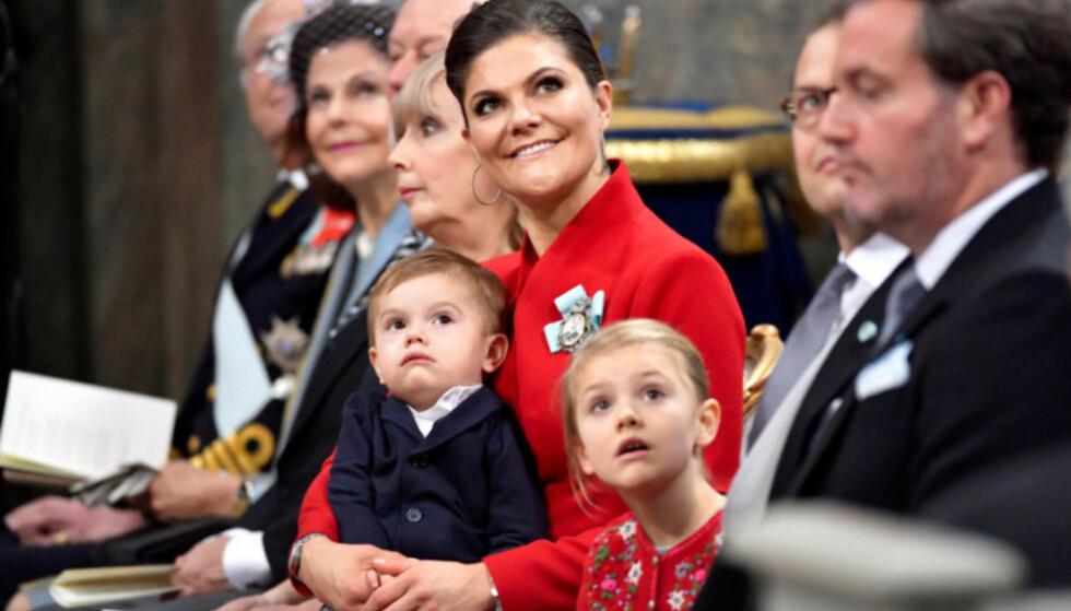 VAKKER: Kronprinsesse Victoria strålte i et julerødt antrekk under nevøens barnedåp i begynnelsen av desember. Datteren prinsesse Estelle var ikledd en grå kjole med en søt, rød cardigan til. Prins Oscar satt rolig på fanget til mamma Victoria, og lot seg tydelig fascinere av musikken som fylte slottskyrkan. Foto: NTB Scanpix