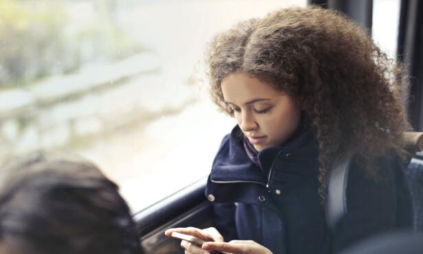 <strong>BUSS = MOBIL:</strong> Med blikket festet på mobilen sitter vi i vår egen verden, og tar sjeldnere og sjeldnere blikket opp for å titte på verden rundt oss. FOTO: NTB Scanpix