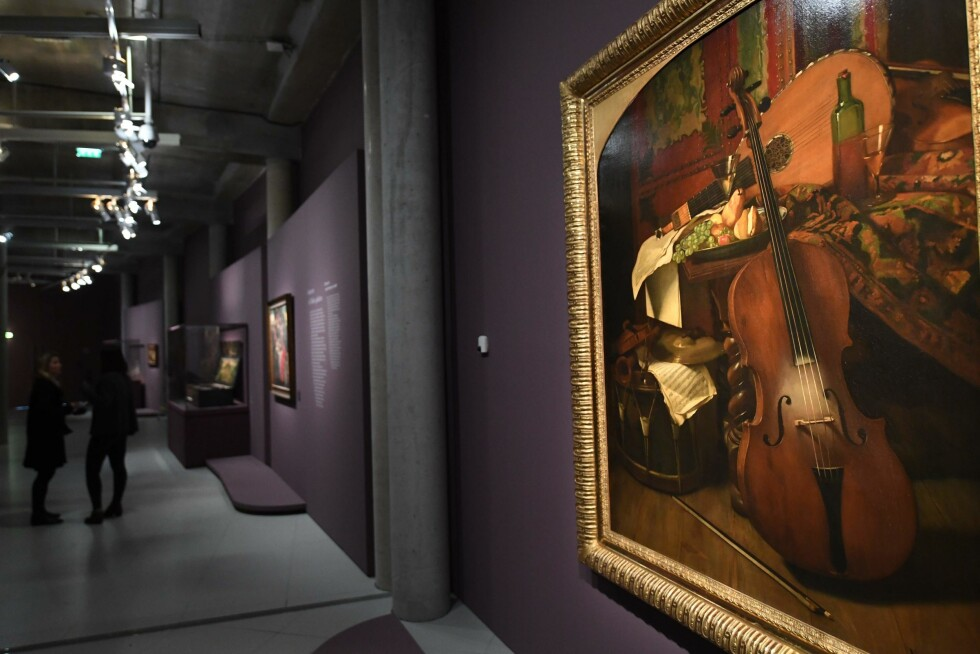 """Visitors stand near the painting """"Still Life with Instruments"""" by Eugene Appert displayed at the exhibition """"Wine and Music, harmony and dissonance (16th-19th century)"""" at the Cite du Vin (Wine Museum) in Bordeaux, southwestern France, on March 21, 2018. Nearly 150 French and European artworks and objects are displayed during the museum's second major exhibition from March 23 to June 24, 2018.  / AFP PHOTO / MEHDI FEDOUACH / RESTRICTED TO EDITORIAL USE - MANDATORY MENTION OF THE ARTIST UPON PUBLICATION - TO ILLUSTRATE THE EVENT AS SPECIFIED IN THE CAPTION"""