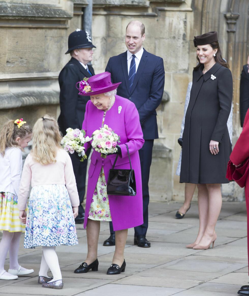 <strong>PÅSKEGUDSTJENESTE:</strong> Hertuginne Kate var til stede under 1.påskedagsgudstjenesten i St. George's Chapel på Windsor Castle med hele den britiske kongefamilien. Her tar dronning Elizabeth imot blomster fra to fremmøtte jenter. Foto: NTB Scanpix