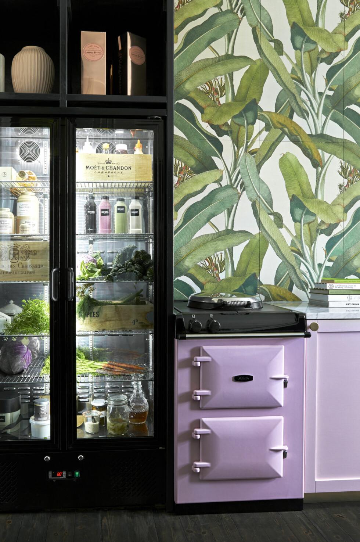 Det krever litt estetisk sans og orden å ha et kjøleskap med glassfronter. Men det er så mye morsommere å lage mat når man kan se alle råvarene ligge der, fristende og vakre, synes familien. Det svarte industrikjøleskapet er egentlig et barkjøleskap funnet på Cateringinventar.dk. Den rosa støpejernskomfyren med to ovner er fra Aga.