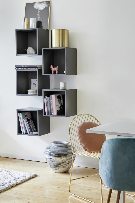 Ved spisebordet har Silke hengt grå bokkasser på veggen. Hun bruker grå nyanser flere steder i leiligheten, da de gir litt motvekt til alle de feminine fargene hun boltrer seg med for tiden. Lignende bokkasser fås hos WalterGrey.dk.