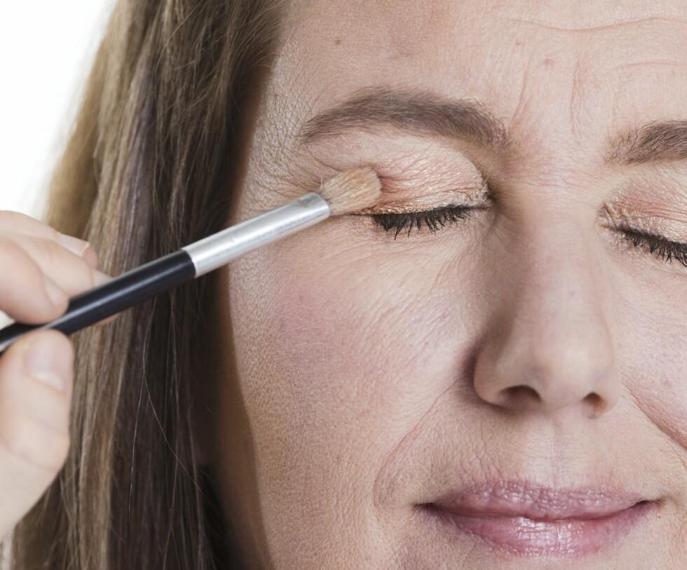 Bruk en myk og rundt kost til å påføre og duse ut øyeskyggen for et naturlig resultat.