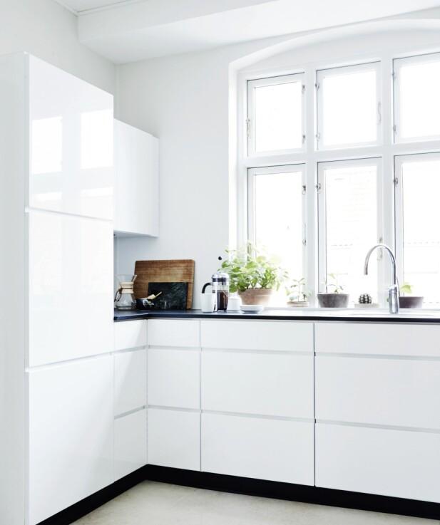 Kjøkkenet er holdt helt enkelt, i tråd med leilighetens minimalistiske uttrykk. Det er et Svane-kjøkken i hvit høyglans med svart bordplate. Slow brew-kaffebryggeren til venstre er fra Chemex, og stempelkannen er fra Bodum. FOTO: Ditte Capion