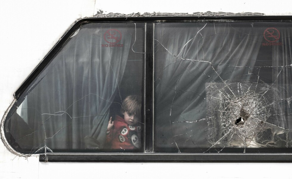 TOPSHOT - A Syrian girl looks through the glass of a window next to another broken pane damaged by objects thrown during the evacuation from the town of Dumayr east of the capital Damascus, as her bus arrives in the city of Azaz in the northern countryside of Aleppo on April 20, 2018. Dumayr, a town lying further from Eastern Ghouta where a reconciliation agreement had kept a security status quo since 2016, was retaken by government forces the day before. A convoy of 31 buses was carrying about 1600 of fighters and civilians arrived in Azaz, while most of the buses headed to Afrin. / AFP PHOTO / Sameer Al-Doumy