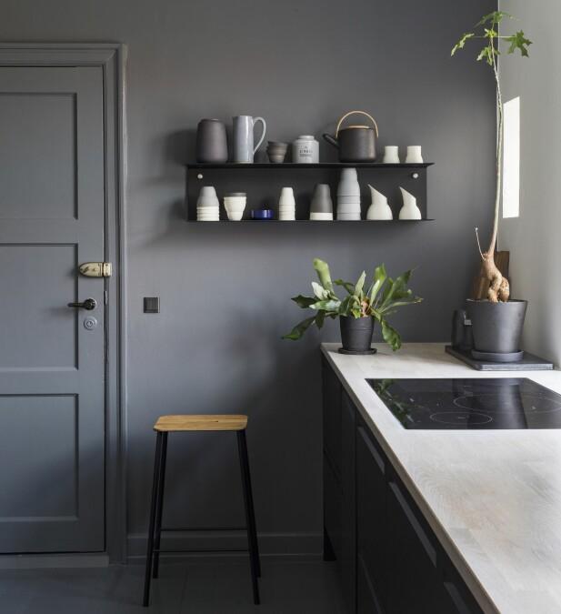 Vegger, gulv, paneler og dør er malt i samme farge. Koppene er fra Vipp, vasen fra Ditte Fischer.Tekannen fra Stelton står på en hylle fra Vipp. Urtepottene er fra Hay. Høystolen fra Frama elsker barna å bruke når Rikke lager mat. FOTO: Andreas Mikkel