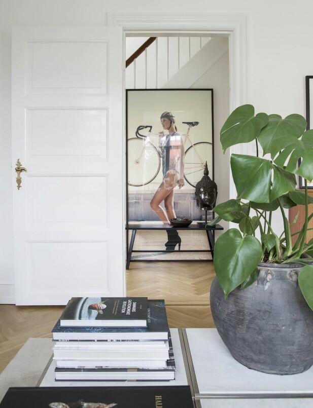 Krukke fra Rosmosegaard Antik, sofabord fra Arne Jacobsen. I bakgrunnen: fotokunst fra The Wall Market, benken er et antikkfunn og buddhafiguren er fra en reise til India. FOTO: Frederikke Heiberg