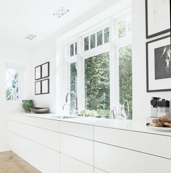 Det enkle uttrykket er skapt ved å velge hvite, minimalistiske kjøkkenelementer som gjør lite ut av seg i de luftige, hvite rommene. Kjøkkenet er fra Invita, kunsten fra Michael Kvium og Christian Lemmertz. FOTO: Frederikke Heiberg