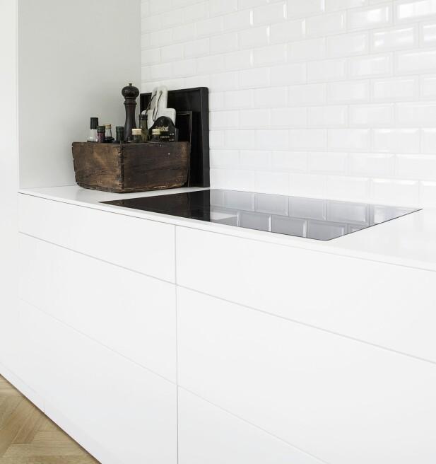 Kjøkkenet er holdt helt stilrent med glatte, hvite fronter uten grep. FOTO: Frederikke Heiberg