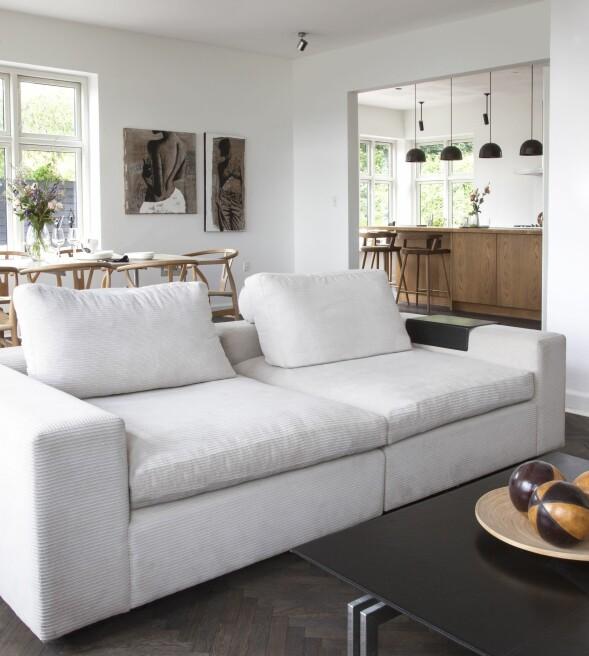 Hvis du har mye lys i boligen, kan det gi en samlende effekt å beise gulvet mørkt. Det gjør også at de lysere møblene blir framhevet. Sofaen er fra Eilersen. FOTO: Iben og Niels Ahlberg