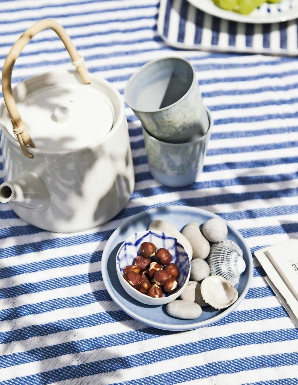 Bruk skjell og stein som pynt på bordet for å få hyttestemningen. Her ligger de på et lite fat sammen med en bolle med nøtter, men du kan også sette telys ned mellom dem. Tekanne, krus og boller fra Stilleben.