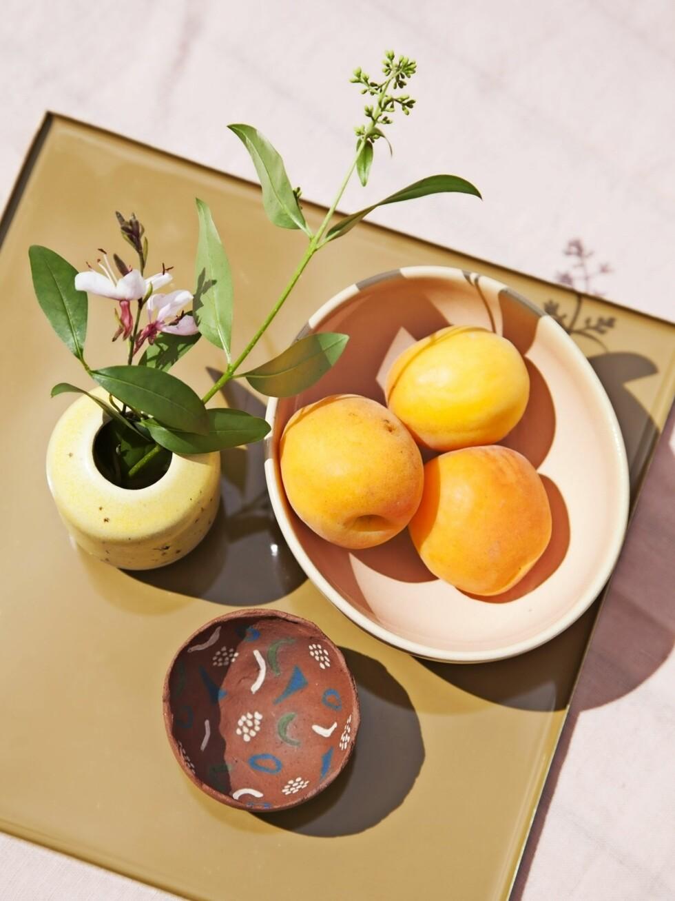 Pynt med organisk dekor som blomster og frukt. Liten, gul vase fra Studio Arhoj og bolle fra Stilleben.