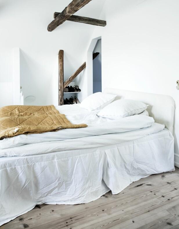 Trebjelkene gir soverommet et rustikt uttrykk. Det gule sengeteppet er funnet på et loppemarked. FOTO: Tia Borgsmidt