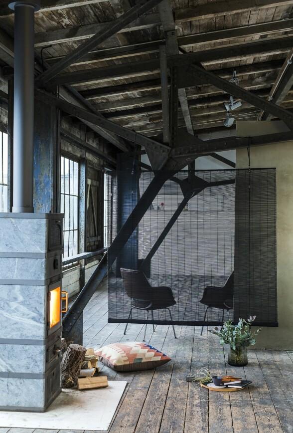 Synlige tak og bjelker i mørkt treverk gir et lunt og tidsriktig preg til interiøret. En perfekt mulighet når loftsleiligheter pusses opp. Her er en bambusgardin fra Color & Co brukt som skillevegg.