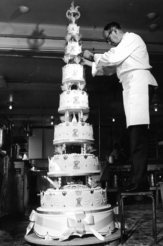 BRYLLUPSKAKEN: Konditormester Rolf Bjerke pynter den 150 kilo tunge bryllupskaken. Kaken var 2,5 meter høy. FOTO: NTB Scanpix