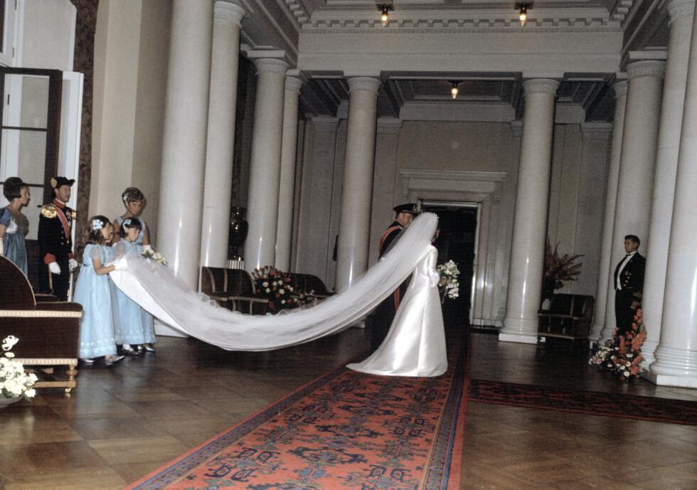 SLØR: Brudepikene hjelper bruden med sløret. Kjolen var kreert av kjolebutikken Molstad, og var i klassisk stil med 3/4-dels armer langt slep og dekorert med hvite perler og broderier. I tillegg kom et stort tyllslør og - en brudebukett i hvitt, med hvite roser, fresia, liljekonvaller og orkidé. FOTO: NTB Scanpix