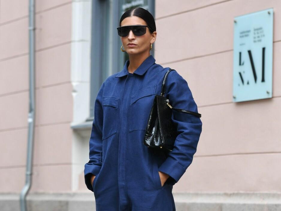 JUMPSUIT: Blogger Katarina Petrovic styler sin blå jumpsuit med en svart veske, solbriller og øredobber i gull. Foto: Scanpix