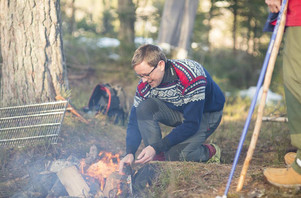 IDYLLISKE OMGIVELSER: Brudgommen Jan-Sigurd Sørensen fyrer opp bålet. FOTO: Mats Andreassen Grimsæth