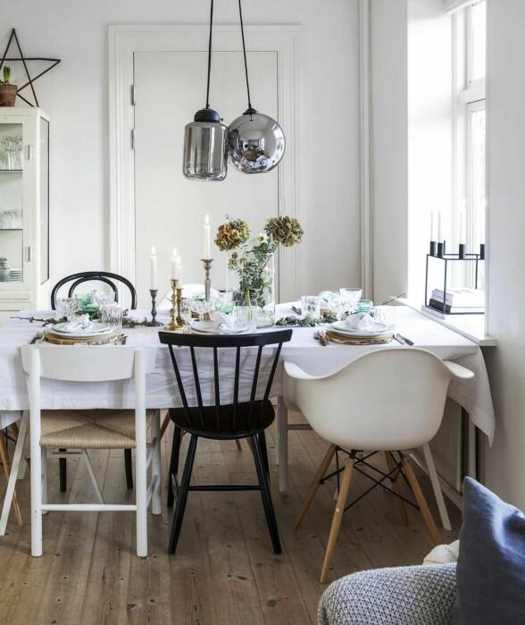 Sjarmerende festbord på kjøkkenet! Spisebordet er en hjemmelaget bordplate med bein fra Ikea. En av spisestolene er Eames og en annen er flettestol fra Børge Mogensen, mens de øvrige er arvegods.