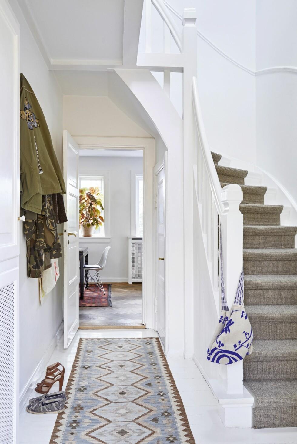 Miks gjerne mønstrete og ensfargete gulvtepper. Så lenge en av fargene fra det ensfargete teppe går igjen på det mønstrete teppet, vil resultatet virke harmonisk, som her i entreen. Her ligger en kokosløper på trappen, mens et kelimteppe pynter opp gulvet.