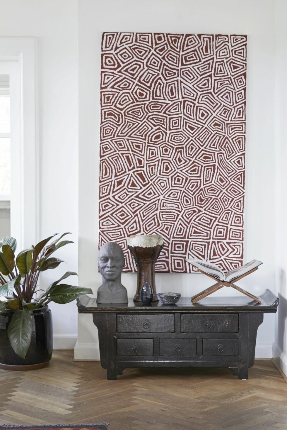 Den gamle kinesiske kommoden er fra Green Square, bokstøtten er kjøpt i Paris, og trommen er fra Marrakech. Bysten, vasen og skålen har Trine selv laget. Maleriet er australsk aboriginsk kunst. Sjekk aboriginalpaintings.dk for lignende.