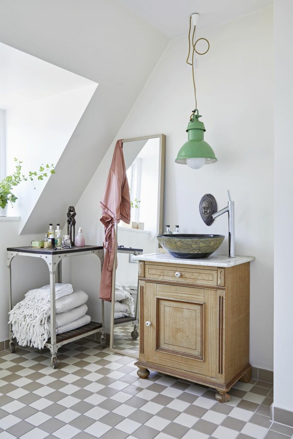 Trine har stilt et gammelt rullebord av metall under skråveggen og har på den måten fått plass til kremer, parfymer og håndklær.
