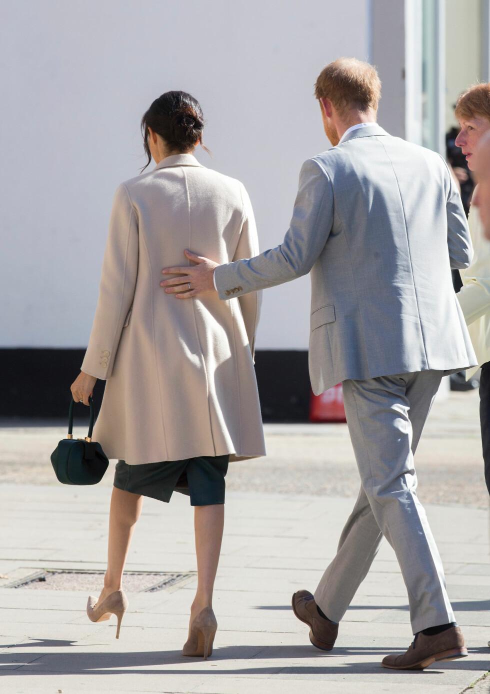 PASSET PÅ KONA: Prins Harry la en beskyttende arm på sin kone under besøket i Sussex. FOTO: NTB Scanpix