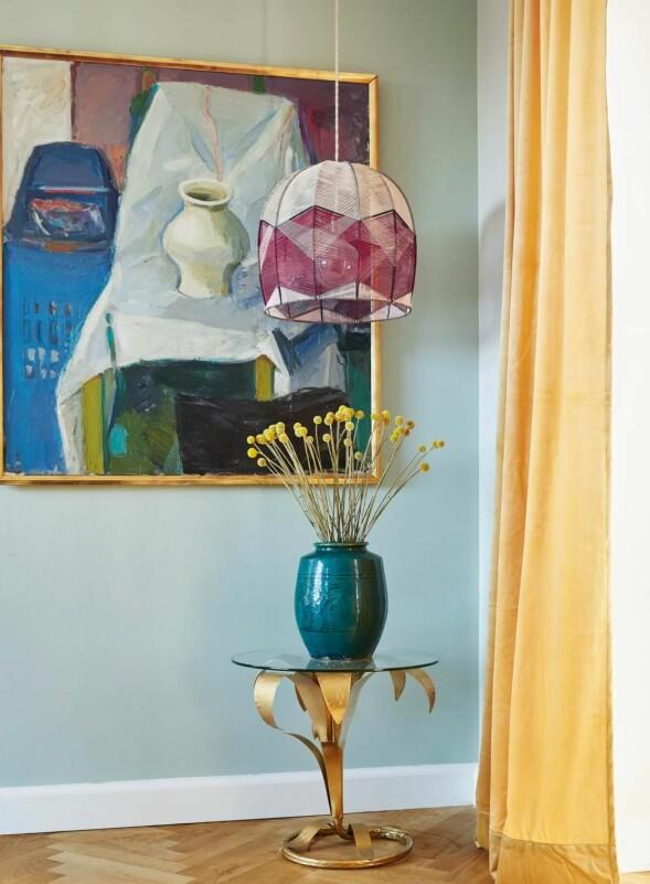 Det fargerike kunstverket er fra Auktionsverket, mens lampen er fra Alexandra Raben. Bord fra Zara Home, vase fra Hay Vintage og gardin fra Ellos Home. FOTO: Stylesystemet