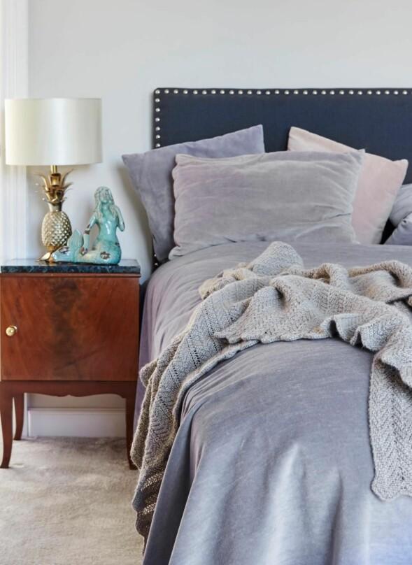 Puter og sengeteppe fra Jesper Holkenberg, pledd fra Aiayu og bordlampe fra Zara Home. Nattbordet er et arvestykke, og havfruen er kjøpt hos Beau Marché. Veggen er malt i fargen Ammonite fra Farrow & Ball. FOTO: Stylesystemet