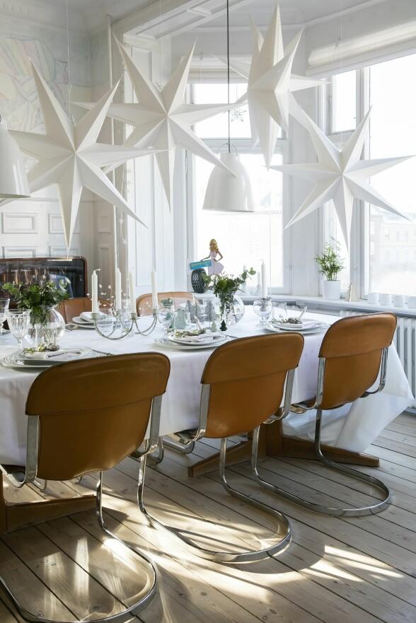 Fie har hengt store stjerner i taket over spisebordet i det lyse karnappet i spisestuen så det virker som en hel stjernehimmel. Stolene er kjøpt på auksjon, og stjernene hos Dora. FOTO: Lise Lotte Plenov
