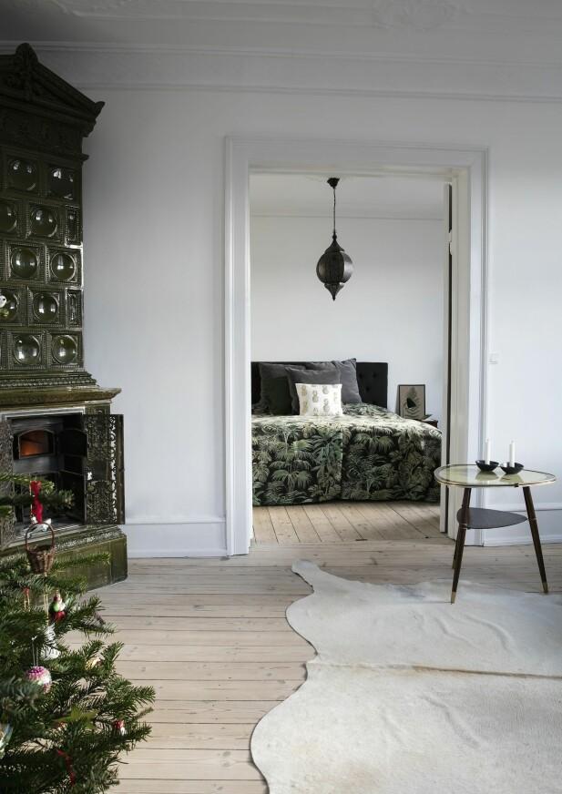 Fargen fra den grønne kaminen blir tatt opp flere steder i huset. Her i sengeteppet med tropisk print. FOTO: Lise Lotte Plenov