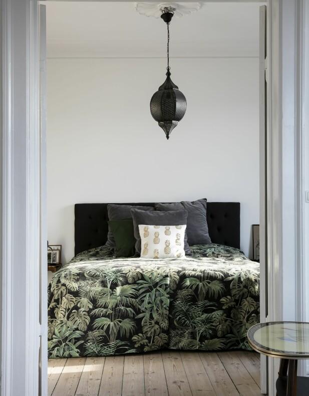 Soverommet er like hyggelig som stuen med en myk, mørk sengegavl, godt med puter og et fantastisk sengeteppe som Fie har sydd selv. Putene er blant annet fra Ikea og H&M. FOTO: Lise Lotte Plenov
