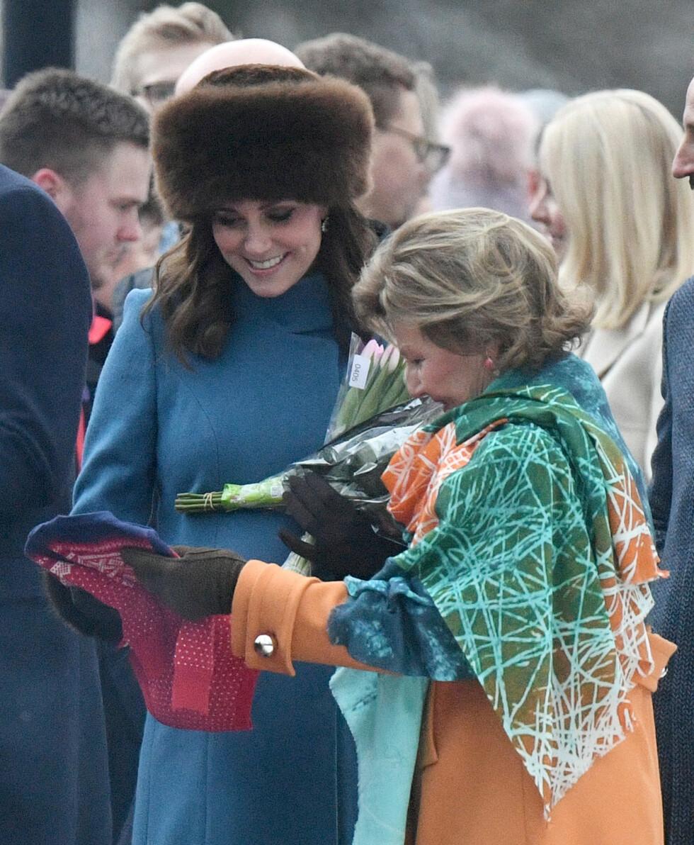 BABYGAVE: Hetruginne Kate var på dette tidspunktet gravid med sitt tredje barn, og hetruginnen fikk flere babygaver av det norske folket, som hadde møtt mannsterke opp for å ta det britiske prinseparet vel imot. Her studerer hun en av gavene sammen med dronning Sonja. FOTO: NTB Scanpix