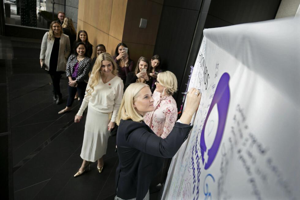 MARKERTE KVINNEDAGEN: Kronprinsesse Mette-Marit tok seg tid til å signere Kvinnedag-tavlen som var plassert ved inngangen til arrangementet på SAP i New York. I bakgrunnen er Anita Krohn Traaseth, administrerende direktør i Innovasjon Norge og Ann Rosenberg, seniorvisepresident i SAP. Foto: Pontus Höök / NTB scanpix