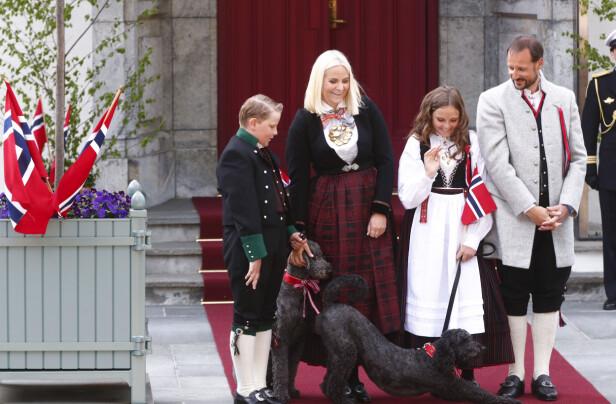 EN LITEN STREKK: Tradisjonen tro vinket kronprinsfamilien til barnetoget foran sin privatbolig på Skaugum på morgenen 17. mai. Hundene Muffins Kråkebolle og Milly Kakao var også med, og sistnevnte hund benyttet anledningen til å gjøre en liten strekk foran barnetoget. FOTO: NTB Scanpix