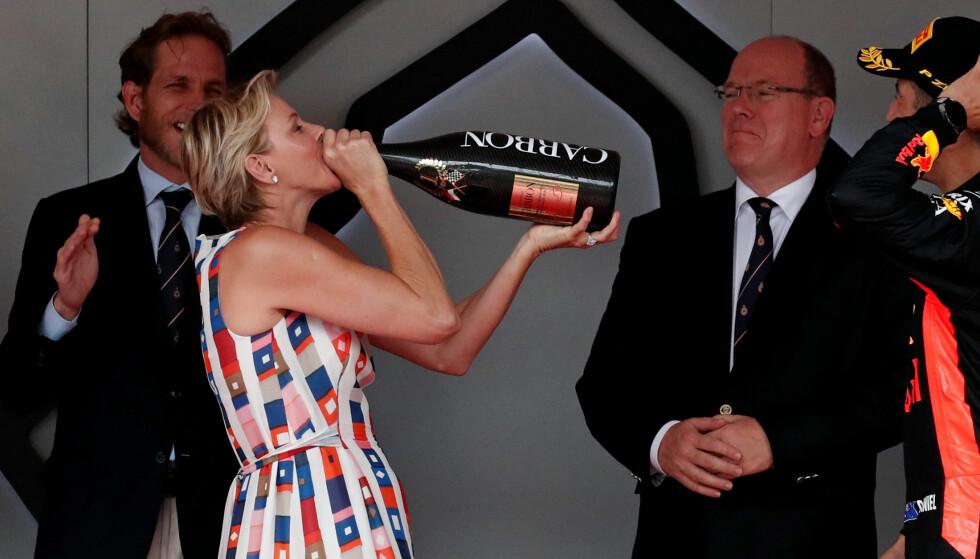 SKÅL!: Prinsesse Charlene av Monaco feiret at Daniel Ricciardo vant Formula One-løpet i mai, med en stor slurk champagne. I bakgrunnen jubler ektemannen prins Albert og nevøen Andrea Casiraghi. FOTO: NTB Scanpix