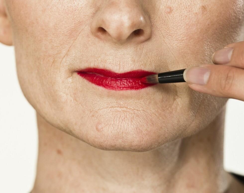 3. Fullfør sminken med fargesterke lepper. Start med å forme og markere leppene med en rød lipliner, og legg også lineren på hele leppen for et langvarig resultat. Avslutt med en rød leppestift som er glossy i finishen.
