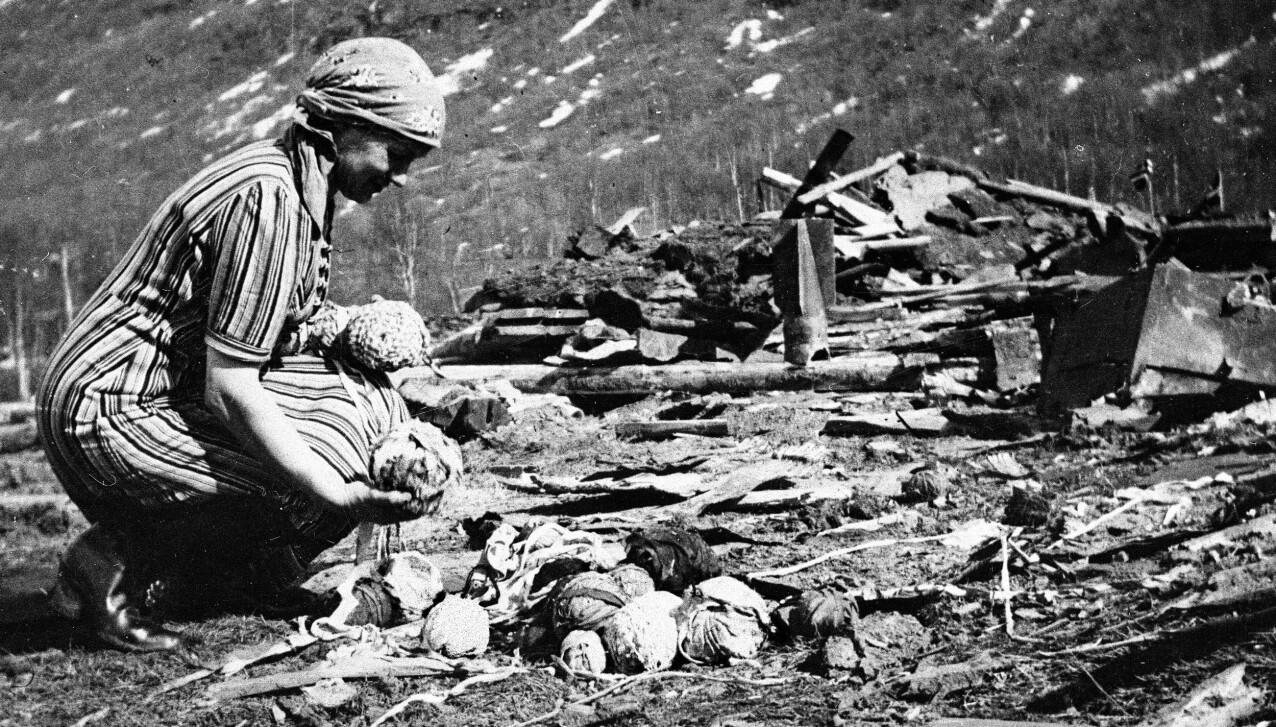 ET HJEM I RUINER: En kvinne fra Narvik er fotografert i ruinene av sitt hjem etter den massive bombingen i den nordnorske byen. Bare noen nøster av gamle tøystykker er igjen. FOTO: gjengitt med tillatelse fra Gyldendal forlag