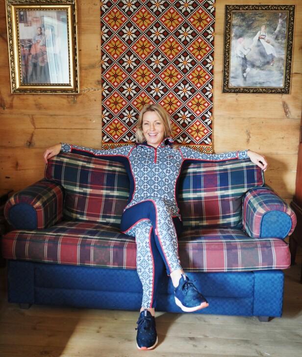 TILBAKE TIL RØTTENE: Kari Traa foran veggteppet på stølen til familien, hvor Rose-mønsteret kommer fra. FOTO: Marianne Huseby